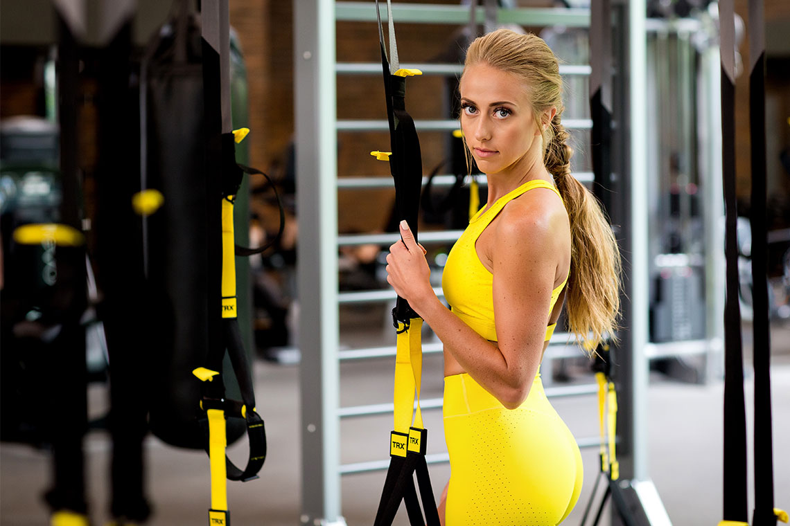 Britt in yellow gym clothes holding exercise straps